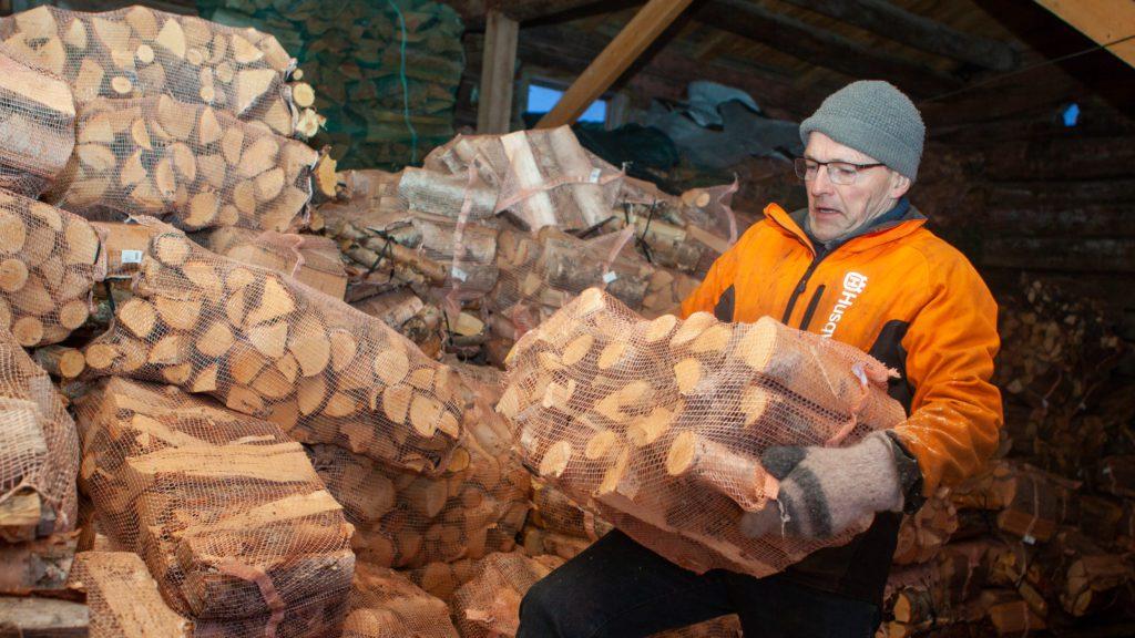 OLA-VED: Ola Hansen Eriksrud (57) lemper ved i vedlageret som stadig minker. Han regner med at bjørkeveden forsvinner i løpet av vinteren. Foto: Lars Vingelsgård